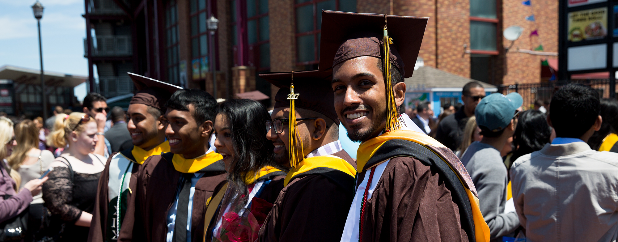 Adelphi graduate smiles in the crowd