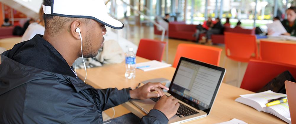 Student using laptop in Nexus at Adelphi